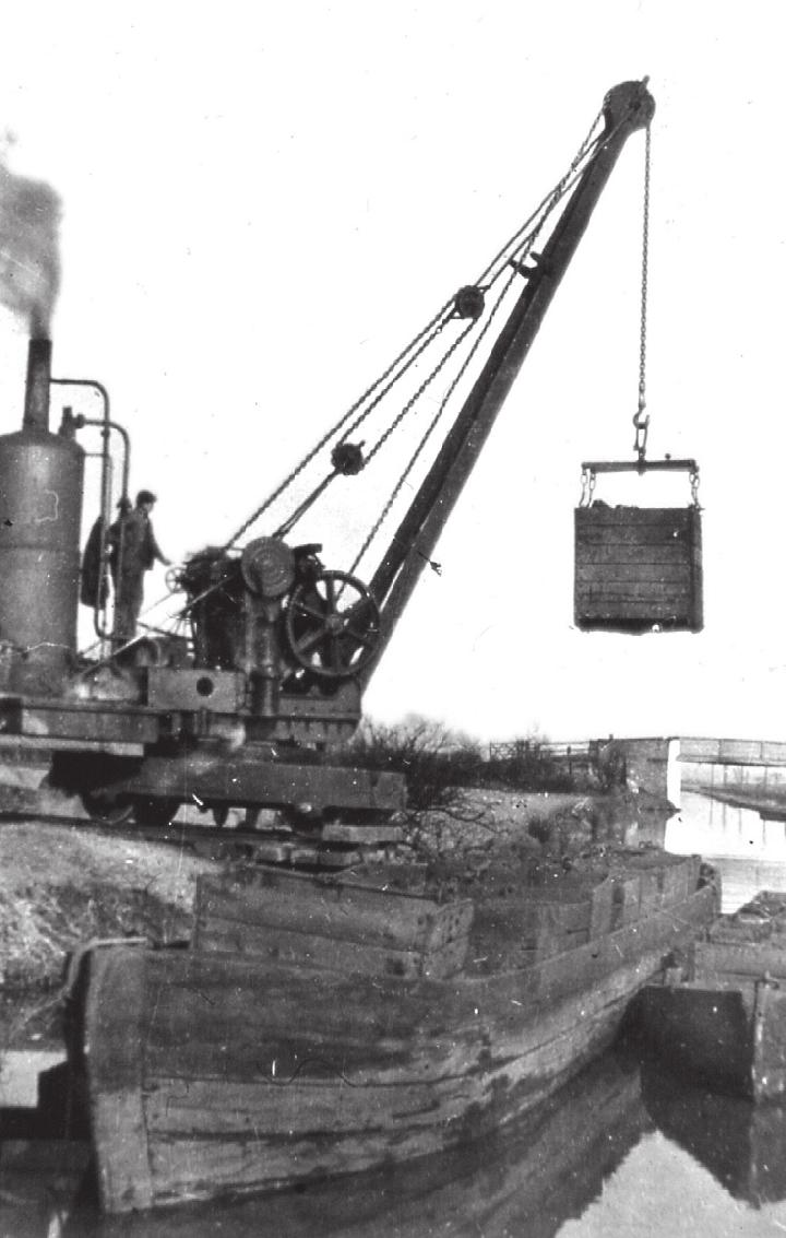 A fine vertical-boilered steam crane being used to load boxes of coal at Astley Green Colliery on the Bridgewater Canal.